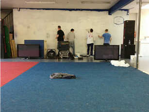 The team painting over a dark blue wall
